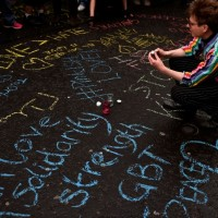 Человек среди граффити в память об убитых в Орландо