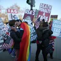 Однополые пары целуются на фоне гомофобных плакатов