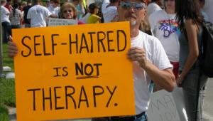 """Мужчина с плакатом """"Ненависть к себе - не терапия"""""""