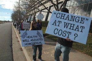 """Протест против NARTH в 2008 году; на плакатах: """"Здоровая, адаптированная гомосексуалка"""", """"""""Изменение"""" - какой ценой?"""""""